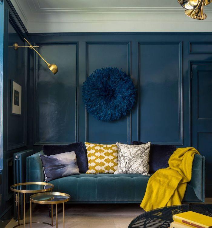 accents jaunes pour peps sans un salon habillé de bleu avec un canapé bleu de vert, coussins décoratifs colorés, parquet bois clair, decoration murale de plumes