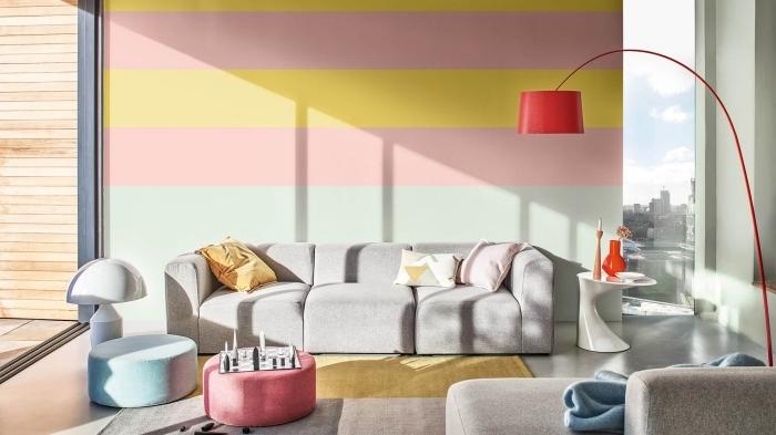deco appartement contemporain aux murs colorés dans un salon au sol béton aménagé avec meubles en tissu gris