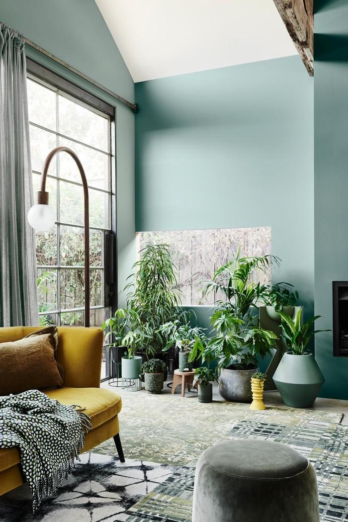 design salon aux murs vert d'eau et plafond blanc décoré de style jungalow aux accents gris et un canapé tendance 2020