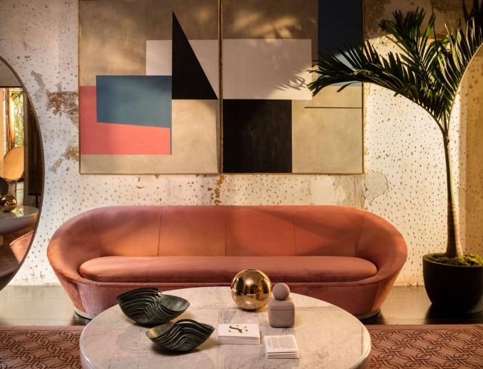 design salon moderne aux murs en papier peint à effet et sol en carrelage beige aménagé avec un canapé tendance 2020 en velours terracotta
