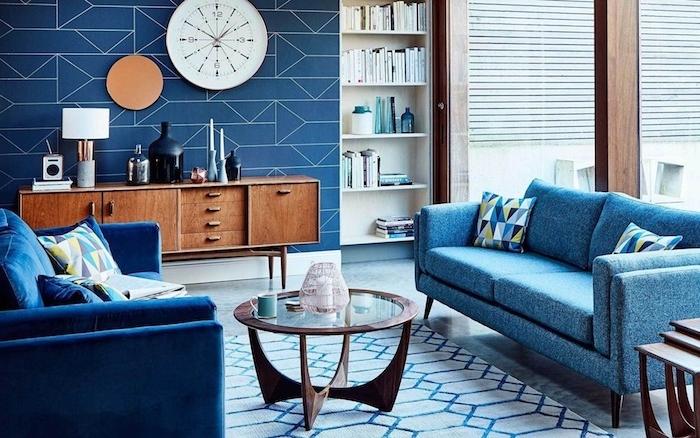 canapés couleur bleue dans un salon bleu et blanc, table basse bois et verre, horloge blanche, meuble tv de bois, tapis blanc et bleu