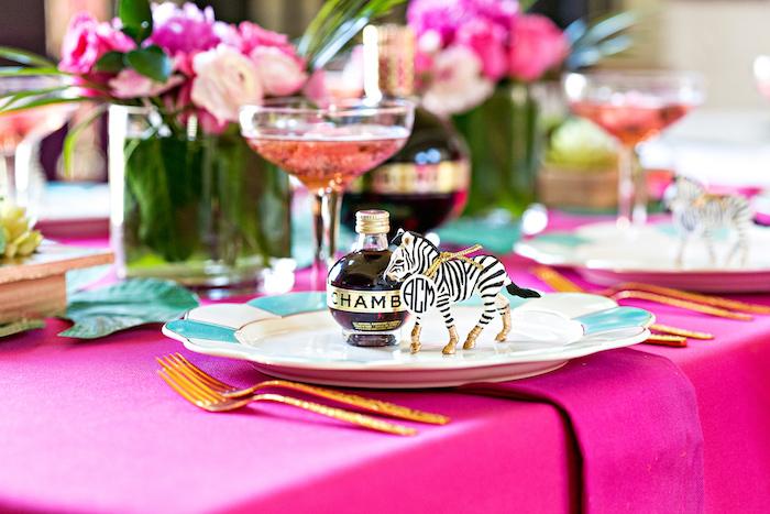 deco de fete tropicale, idee centre de table fleurs rose et fuchsia, nappe couleur fuchsia, marque place anniversaire zebre figurine