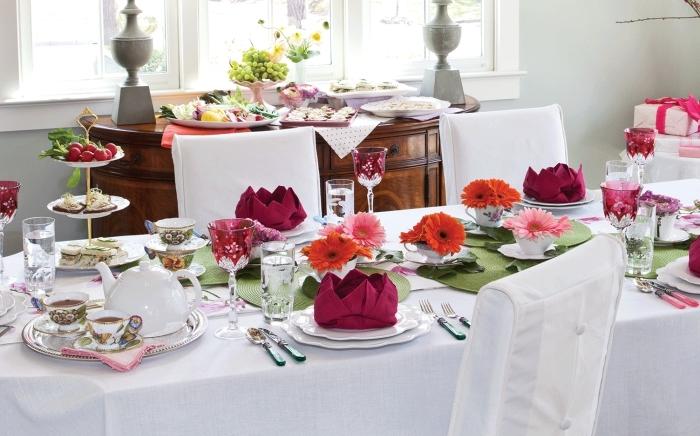 exemple comment décorer une table festive en blanc et rouge, idée de pliage de serviette en papier sous forme de lotus