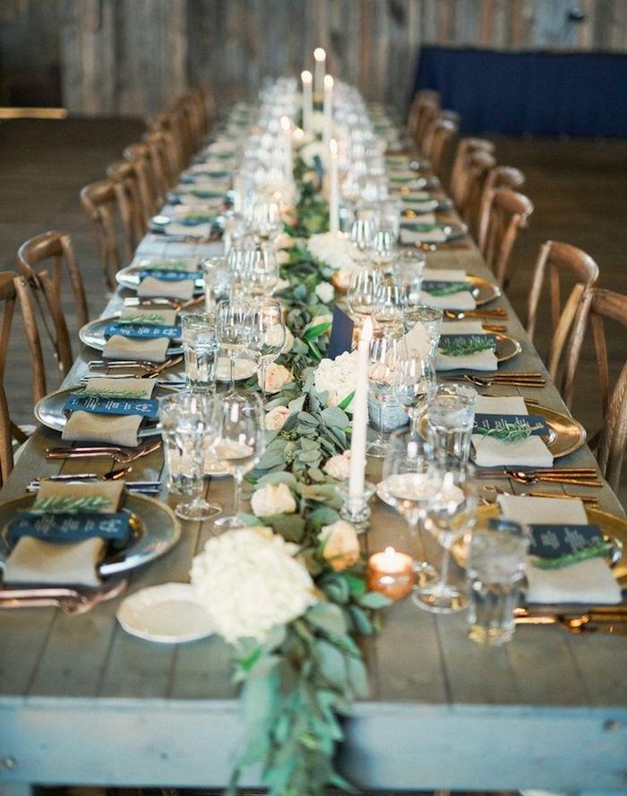 centre de table en guirlande de laurier et fleurs sur table bois brut, assiettes et couverts dorés, menu inscrit sur papier noir, bougies décoratives, deco table mariage champetre