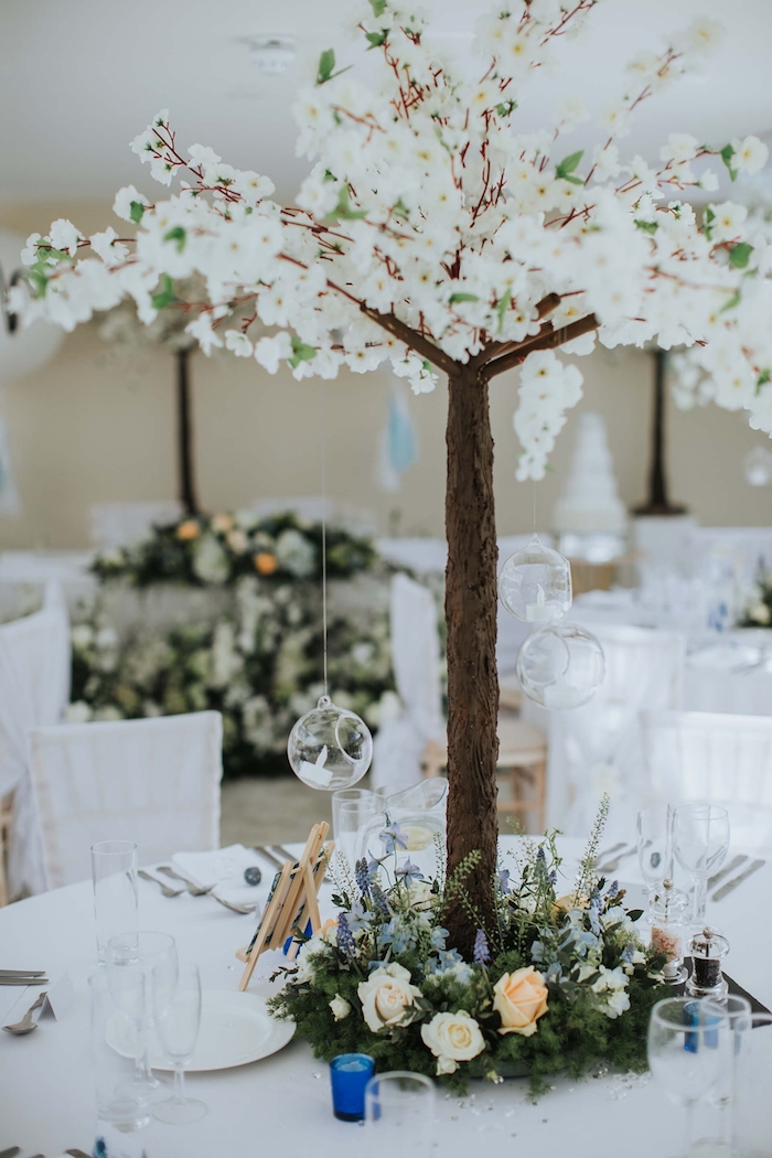 centre de table petit arbre fleuri de fleurs blanches, cerisier fleuri avec lumières suspendues et fleurs aux pieds, idee decoration mariage centre de table