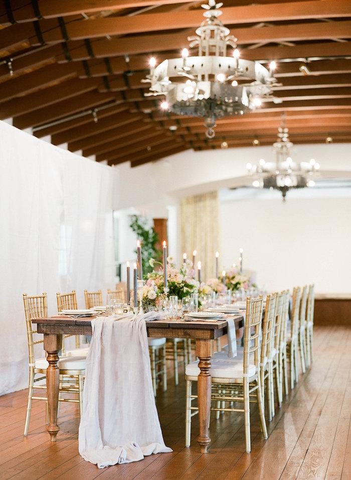 poutres apparentes et lustres industriels dans une salle de mariage vêtue de bous avec table bois brut et chemin de table toile, bougies decoratives, theme de mariage vintage industriel