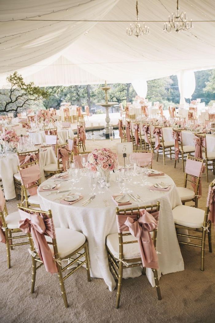 deco chaise décorée de ruban rose, centre de table en fleurs rose et serviettes roses, tapis gris, plafond décoré de voiles blanches