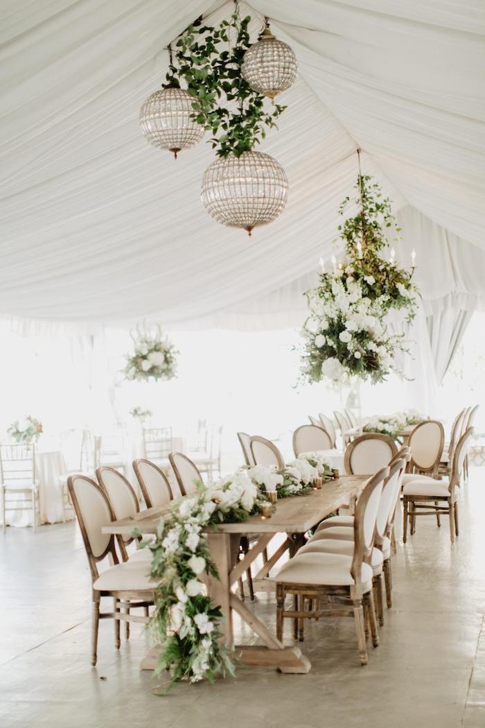 lustre or et verre et végétation suspendue au dessus de table bois clair décorée d une guirlande feuillages et fleurs blanches, draperie plafond blanche
