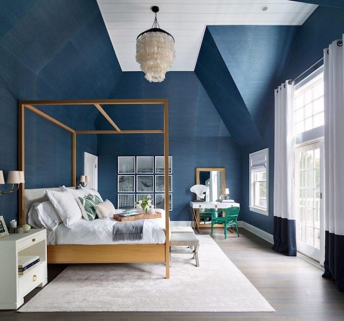 couleur peinture chambre aux murs bleu foncé, suspension originale, lit baldaquin de bois, tapis blanc, parquet gris, deco cadres noir et blanc