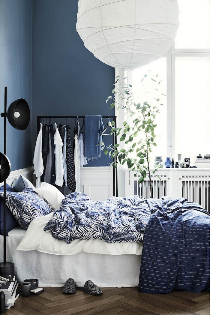 deco chambre cocooning bleu et blanc, chambre avec parquet bois foncé, penderie ouverte, suspension blanche de toile