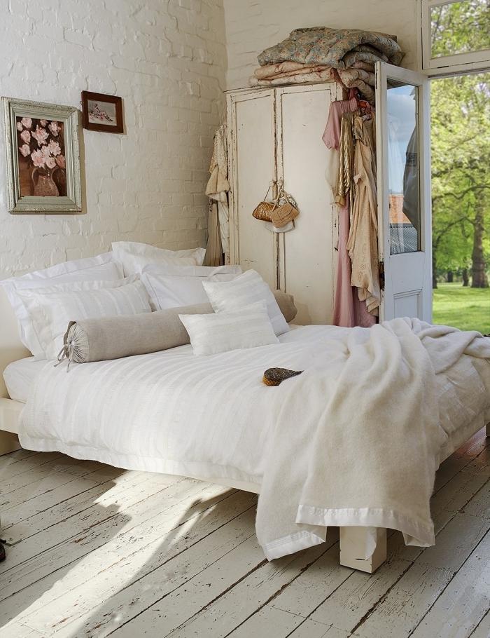 design intérieur style campagne dans une pièce aux murs blancs avec parquet bois blanc aménagé avec grand lit cozy