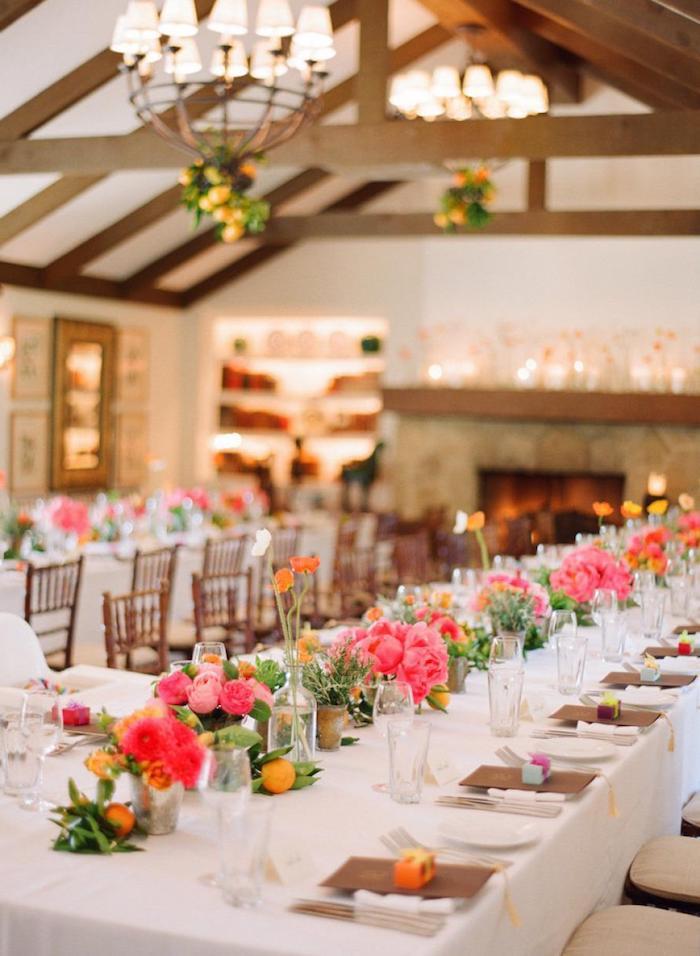 centre de table en fleurs rose et fuchsia et clementines, branches de citron suspendues, idee decoration mariage colorée en couleurs vitaminées