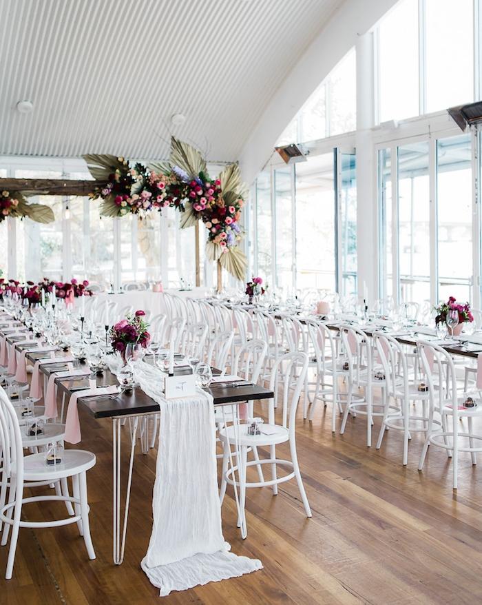 guirlandes et bouquets de fleurs rose et rouges dans salle de mariage blanche avec parquet clair, chemin de table toile blanche, idee deco mariage classique