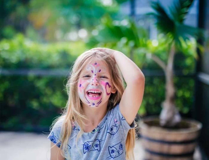maquillage enfant simple pour un party d'anniversaire, idée comment dessiner le visage d'une fille avec crayon à motifs coeurs et fleurs