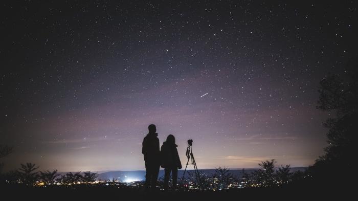 idée de sortie en amoureux originale, couple amoureux qui observe le ciel nocturne sur un colin avec une vue sur la ville