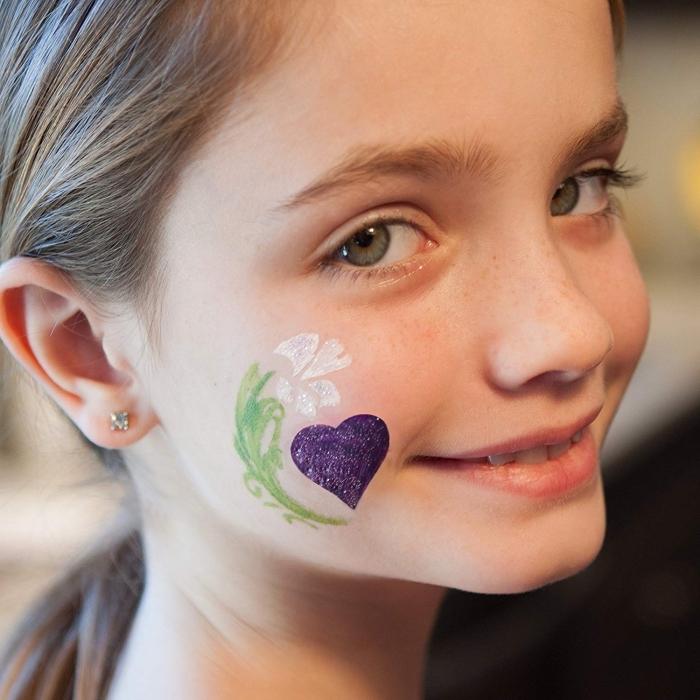 maquillage carnaval minimaliste pour petite fille avec peinture faciale à effet glitter et à design fleur blanche et petit coeur violet