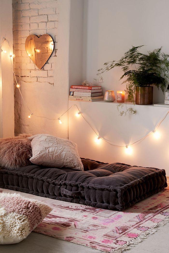 Installer un petit matelas sur le sol entouré de coussins et guirlande lumineuse, coeur miroir sur mur blanche en briques, decoration fete, déco table st valentin, soirée saint valentin