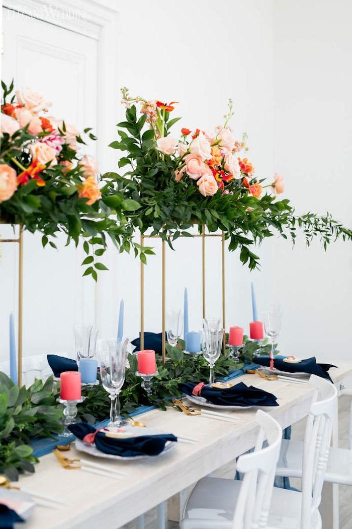 composition florale de mariage en hauteur sur piliers or, chemin de table aux feuillages verts et bougies rose sur supports de verre, idee decoration mariage élégante