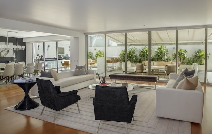 Aménagement grand espace design, salle de séjour avec deux canapés, deux fauteuils noirs, tapis blanc rectacngulaire