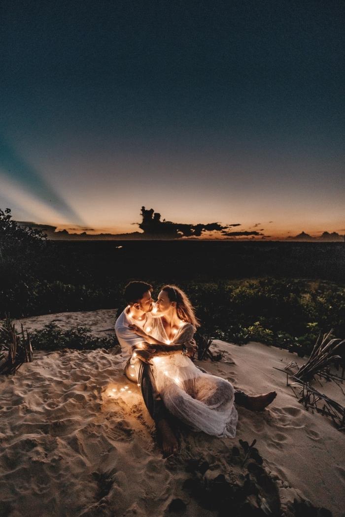 idée de sortie en amoureux originale, couple amoureux habillés en blanc et assis sur le sable au coucher du soleil