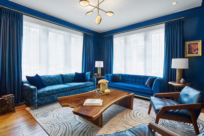 couleur tendance 2020 peinture bleu classique, deco salon luxe avec canapés bleus, murs et rideaux bleus, suspension originale tapis blanc et gris