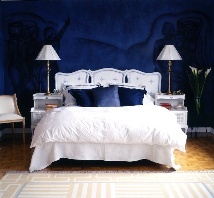 couleur bleu nuit en peinture murale à motifs silhouettes humaines, linge de lit blanc et coussins bleu nuit, parquet bois clair