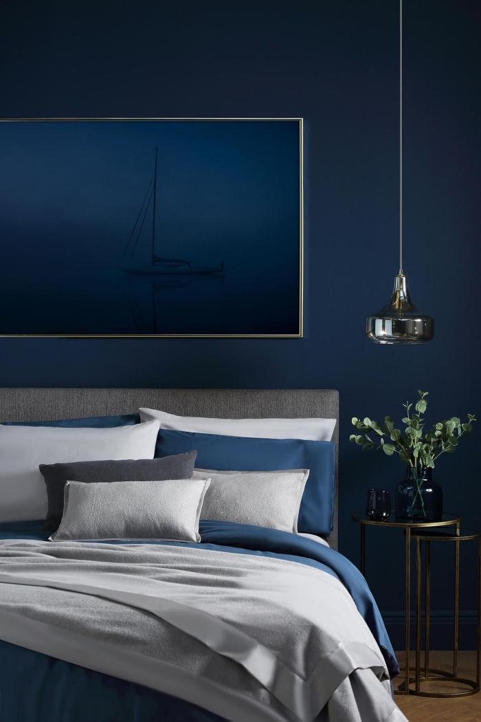exemple de deco chambre parentale contemporaine aux murs bleu nuit aménagée avec lit gris et meuble de chevet métal