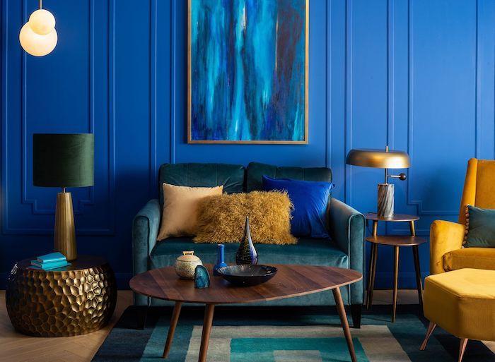 couleur tendance 2020 peinture, murs couleur bleu nuit et canapé bleu petrole, fauteuil jaune, parquet bois clair, tapis vert, bleu et beige