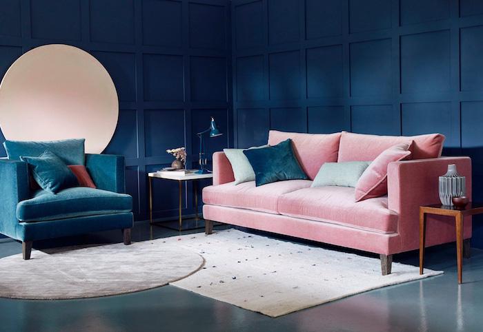 murs couleur bleu nuit, fauteuil bleu foncé et canapé rose dans un salon bleu foncé, tapis rectangle et tapis rond bleu et gris, coussins decoratifs colorés, table de service bois