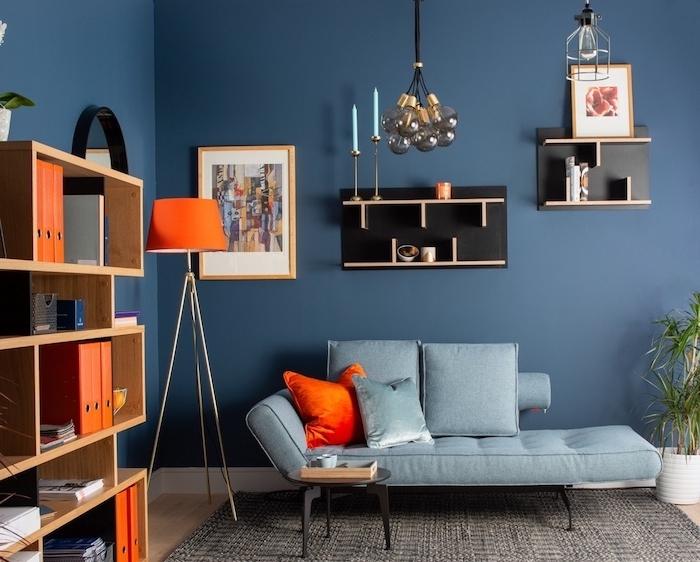 deco maison contemporaine avec salon bleu nuit aux accents orange, coussin, lampe orange, étagère originale couleur noire, suspension boules de verre