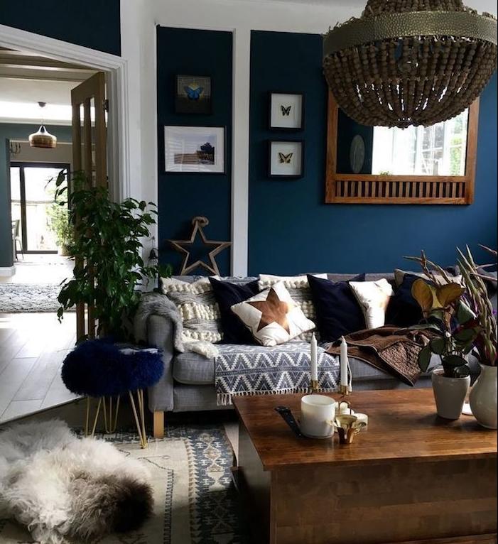 lustre elegant dans un salon bleu nuit avec canapé gris, coussins decoratifs bleu, blanc et marron, plaid gris, table basse bois