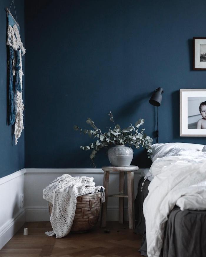 couleur peinture salonbleu nuit aux accents blancs, linge de lit gris et blanc, table de nuit tabouret de bois, vase avec branches vertes, macramé mural