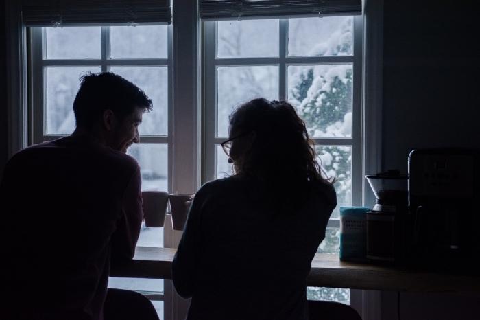 activité en couple, couple amoureux qui boivent chocolat chaud devant une grande fenêtre avec vue vers des arbres enneigés