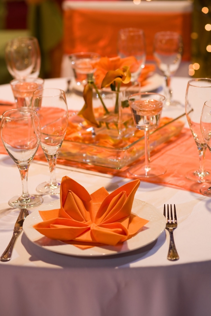 réaliser une fleur de lotus facile avec serviette en papier orange, arrangement de table stylée en blanc et orange