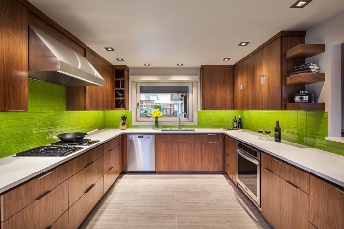 design intérieur moderne dans une cuisine aux murs blancs aménagée avec meubles en bois foncé et crédence vert anis