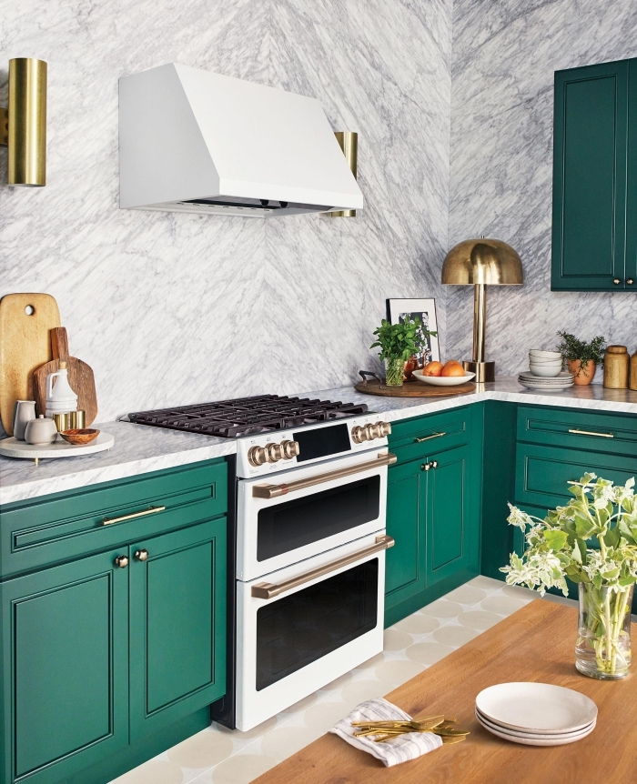 modèle de cuisine contemporaine aux murs à effet marbre blanc aménagée avec armoires de nuance verte et accents dorés