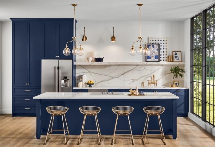 idee deco cuisine blanche au sol en bois avec crédence marbre et meubles en bleu marine, comment décorer une cuisine en longueur avec îlot