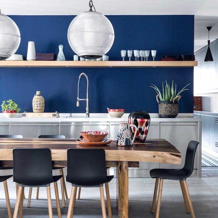 couleur bleu nuit dans une cuisine avec meuble bas blanc, table bois avec chaises noir et bois, étagère bois ouverte, suspension boule de verre