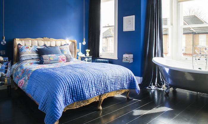 baignoire gris clair dans une chambre à coucher adulte bleu foncé, lit baroque avec linge bleu à imprimé floral, parquet noir