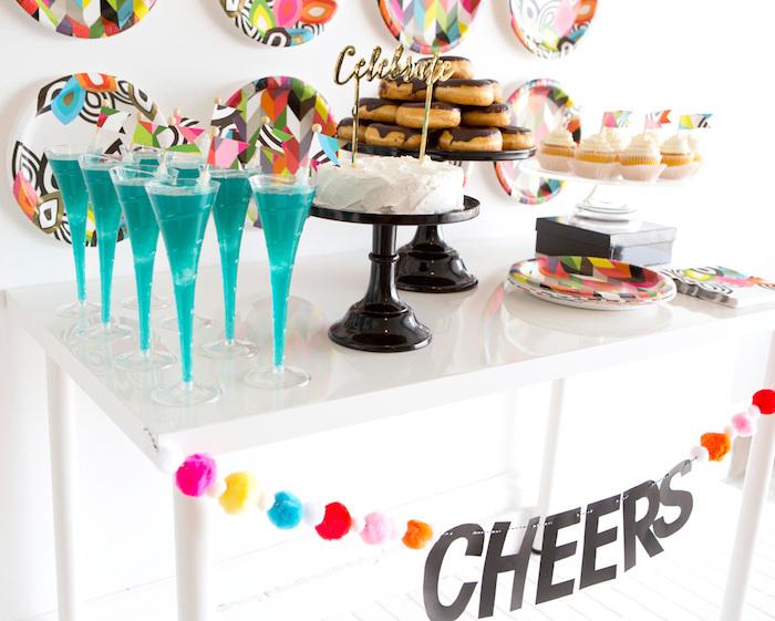 candy bar anniversaire avec deco fond d assiettes colorées, beignets, cupcakes et gateau anniversaire, cocktails bleus, guirlande à pompons colorés