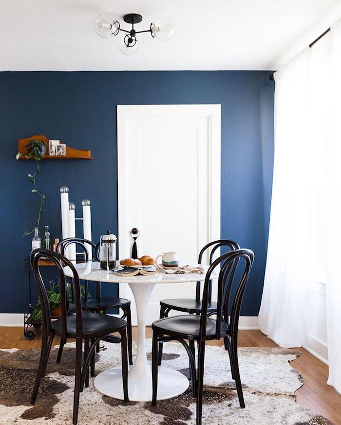 deco salle à manger avec mur de fond blanc, table ronde blanche, chaises noires sur peau mouton tapis marron et blanc, rideaux blancs transparents