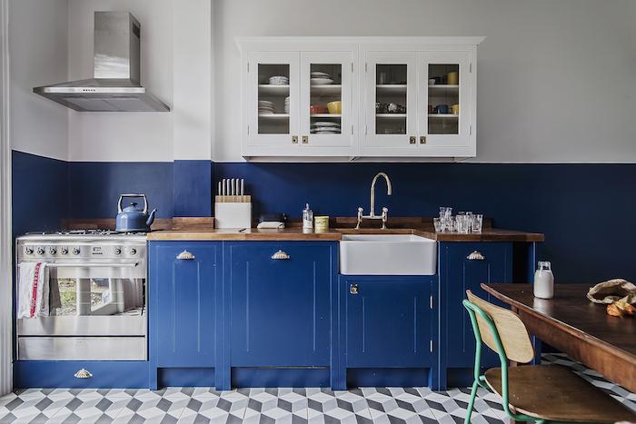 deco cuisine vintage avec meuble cuisine bleu nuit et peinture murale bleu et blanc meuble haut blanc, carrelage gris et blanc, table bois brut