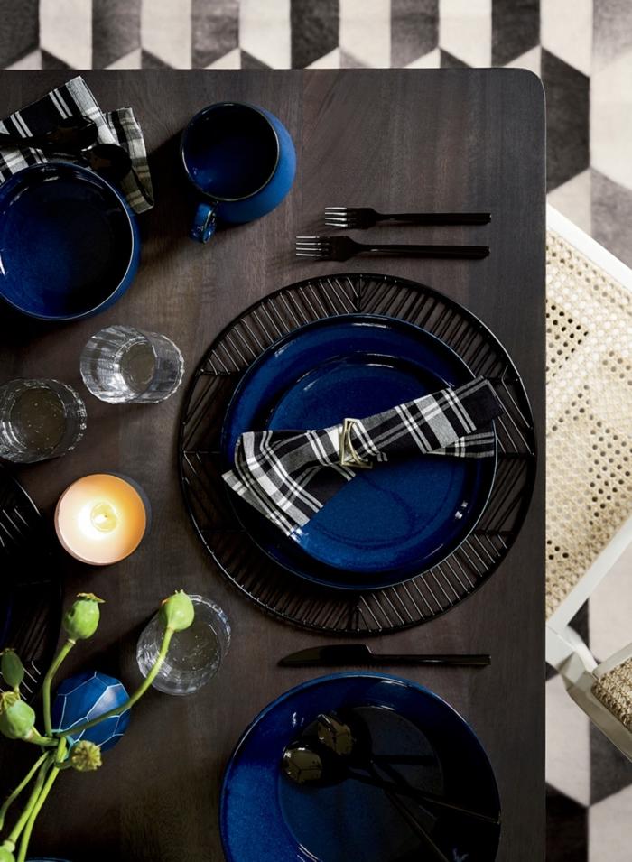 exemple comment décorer une table festive de style moderne avec couverts en noir et assiettes en bleu marine, pliage serviette tissue