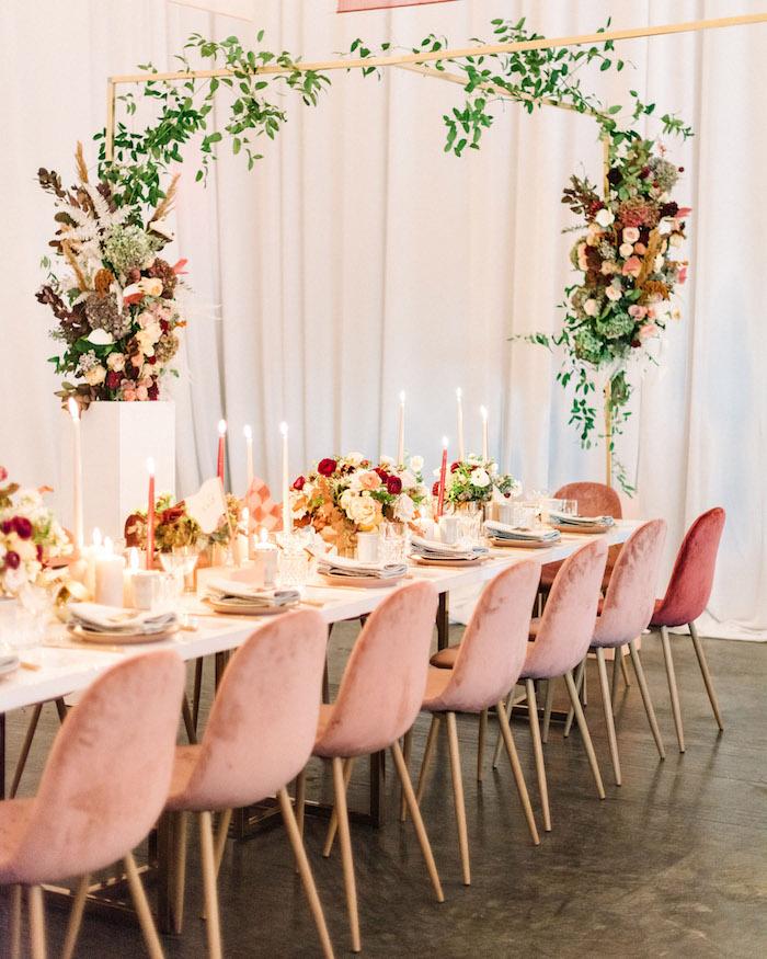 chaises rose rangées autour d une table blanche, deco boheme chic mariage avec compositions florales riches, deco bougies decoratives