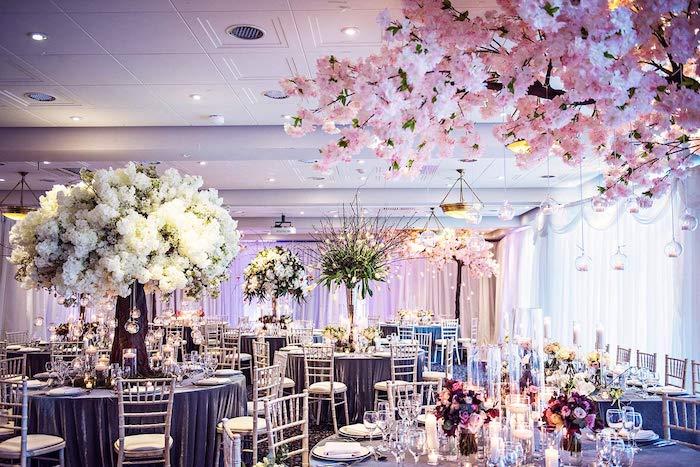 riche décoration florale de fleurs blanches et roses, nappes grises sur table et rideaux blancs, bougies decorative,theme mariage floral