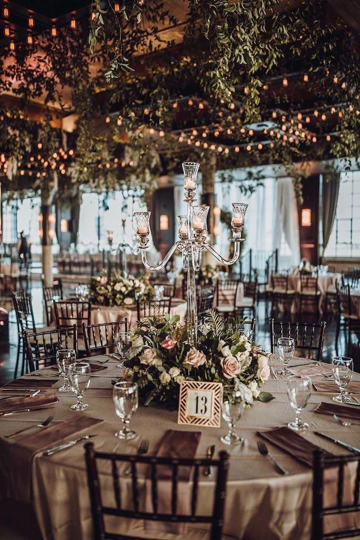 centre de table mariage en végétation verte et fleurs rose, plafond végétalisée et illuminée par guirlandes lumineuses, bougeoirs en verre, idee deco mariage romantique