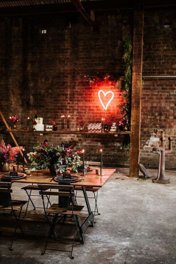idée thème mariage industriel chic dans salle de mariage industrielle, déco coeur néon sur murs de briques, chaises et table industrielle en bois et métal, déco florale en vert et rouge