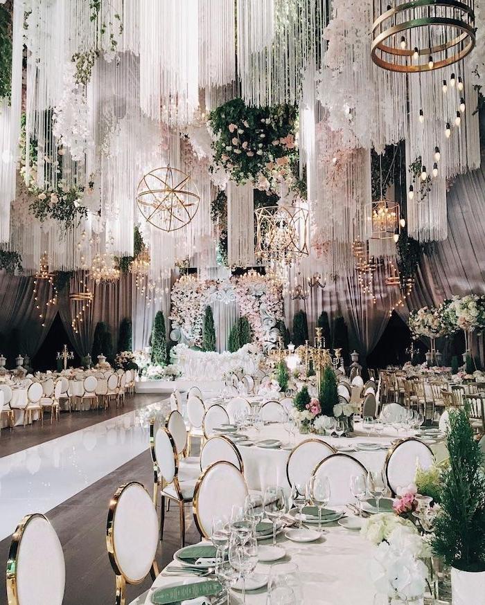 décoration suspendue du plafond, chutes de fils blancs et lustres dorés originaux, chaises blanc et or autour de tables blanches aux accents verts, idee decoration mariage somptueux