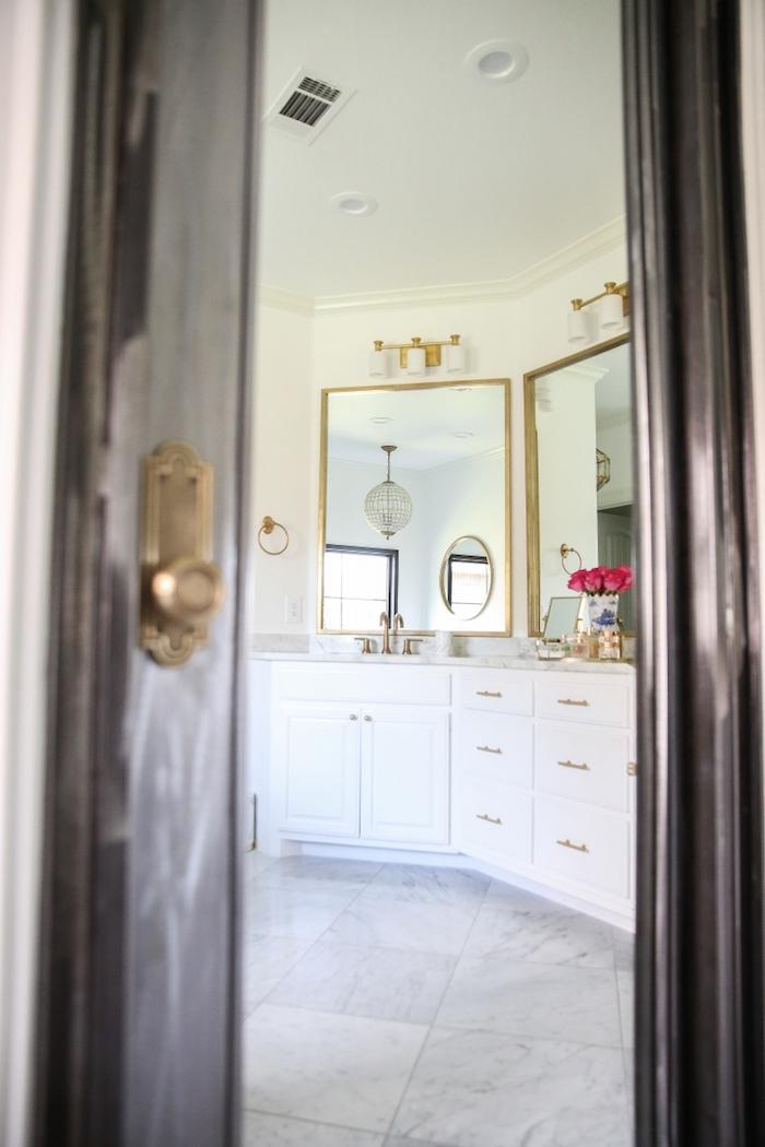 Vue de la porte ouverte à la salle de bains avec sol en marbre, peinture murale blanche, miroirs dorés, meuble lavabo blanc bien rangé, fleurs dans une vase