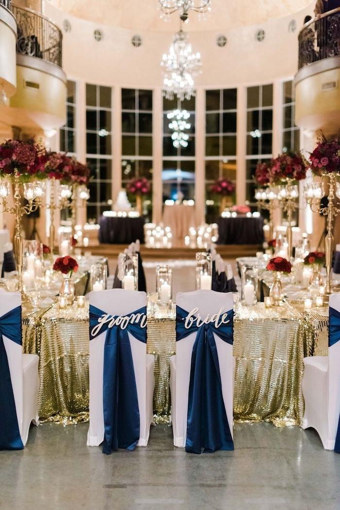 composition florale bouquets de fleurs rose et rouges, tables en nappes or pailletées et chaises blanches décorées de rubans tissu bleu